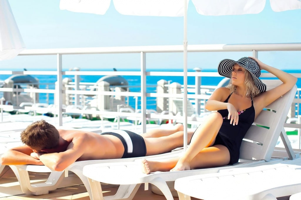 man and woman lying on chaise lounges on a cruise ship