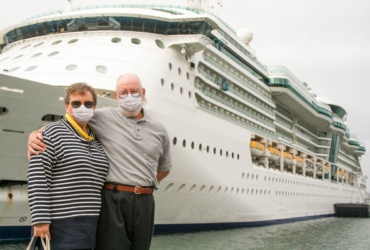 Senior Couple Wearing Face Masks Standing In Front of Cruise Ship